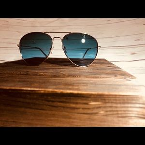 Teal aviator sunglasses with gold frames.